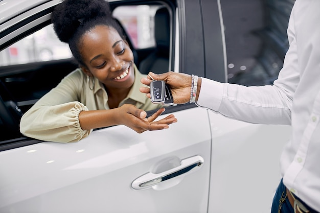 Salesman in dealership give long-awaited keys to black woman sitting in car Premium Photo