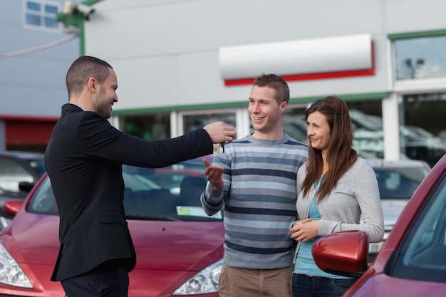 Salesman giving car keys to a couple Premium Photo