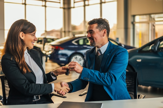 Salesman giving car keys while shaking hand of a woman in a car salon. Premium Photo