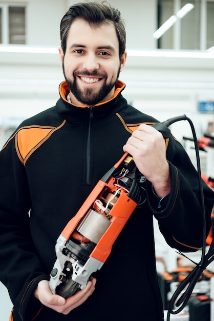 Salesman is holding new disc grinder in aisle Premium Photo