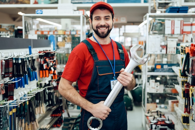 Salesman is posing with new giant wrench in store. Premium Photo
