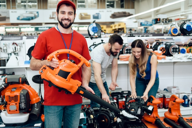 Salesman is posing with new leaf blower with couple. Premium Photo