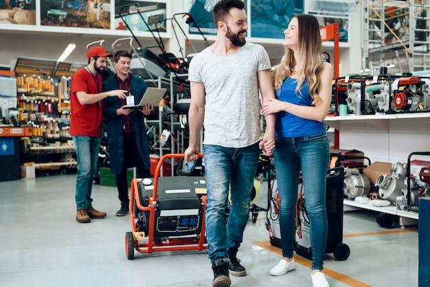 Salesman is showing couple of clients new generator. Premium Photo