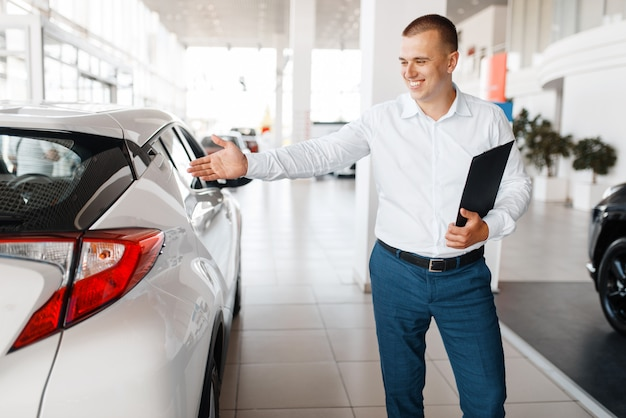 Salesman shows new car in showroom. male customer buying vehicle in dealership, automobile sale, auto purchase Premium Photo