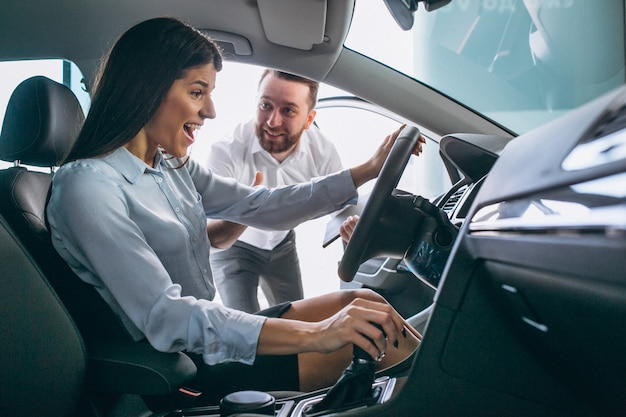 Salesman and woman looking for a car in a car showroom Free Photo