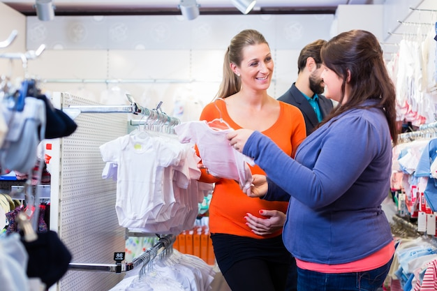 Salesperson with couple buying baby clothes in shop Premium Photo