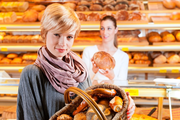 Salesperson with female customer in bakery Premium Photo