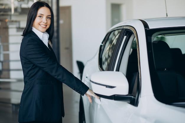 Commessa in autosalone che vende automobili Foto Gratuite