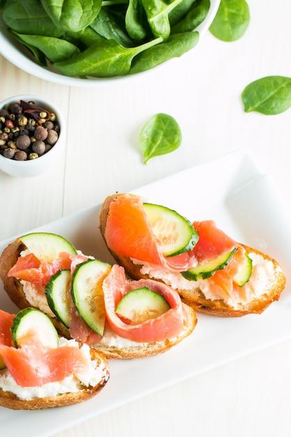 Salmon, cucumber and cream cheese bruschetta. Premium Photo