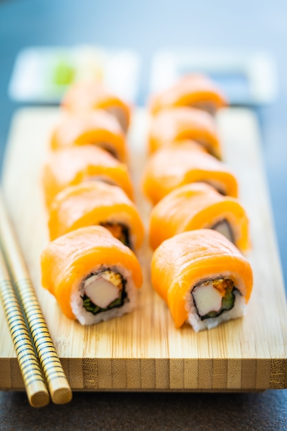 Salmon fish meat sushi roll maki on wood plate Free Photo