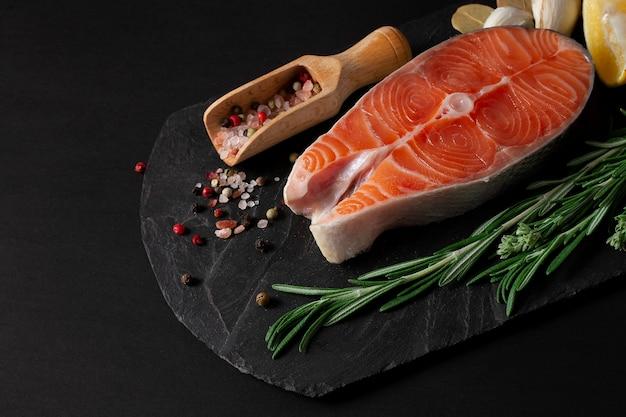 Стейк из лосося со специями на черном фоне Premium Фотографии