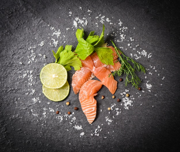 Salmon salad  fish salmon fillet on black plate background top view of raw salmon sashimi seafood with lemon herbs and spices Premium Photo