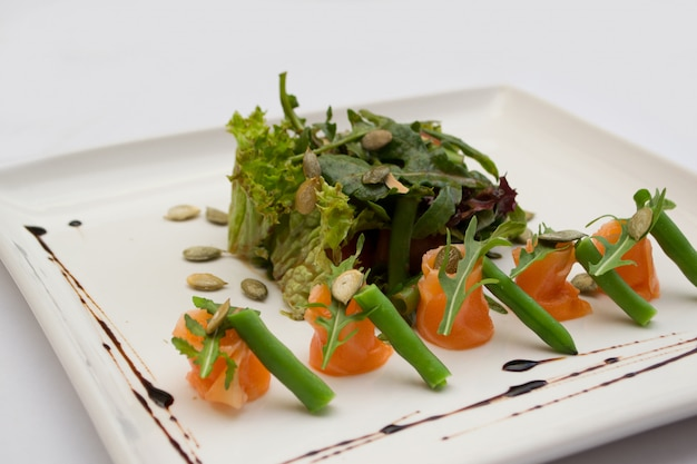 Salmon salad, pumpkin seeds and asparagus on a plate Premium Photo