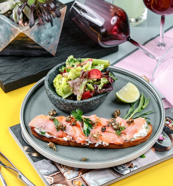 Salmon sandwich with vegetables in the plate Free Photo