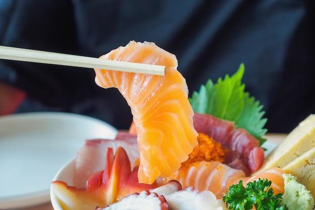 Ломтик лосося в палочках для еды, еда сашими рис чираши дон японская кухня Premium Фотографии