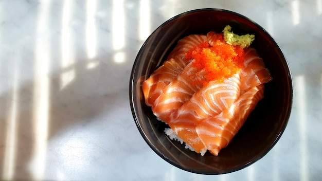 Salmon sushi rice ja panese food in a bowl on the table and copy space Premium Photo