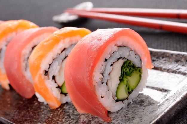 Salmon sushi roll with chopsticks closeup Free Photo