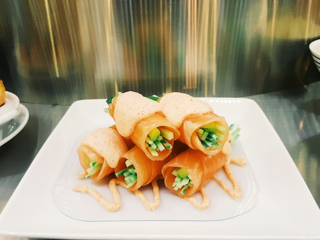 Salmon sushi roll with cucumber inside and topped up with