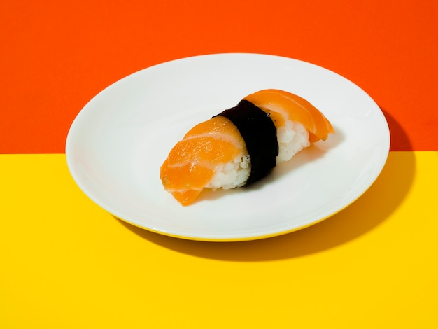 Salmon sushi on a white plate on a yellow and orange background Free Photo