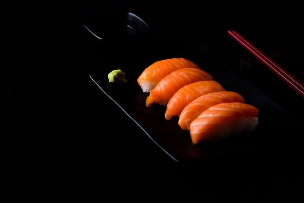 Salmon sushi with green wasabi on black plate or dish and shoyu sauce Premium Photo