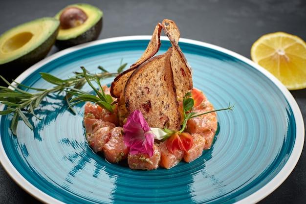 Тартар из лосося с авокадо, на тарелке в голубую полоску, с лаймом и гренками Premium Фотографии