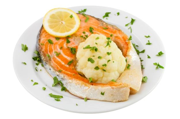 Salmon with cauliflower on the plate on white background Premium Photo