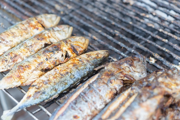 Salt-crusted grilled seabass fish grill on charcoal stove for sale at thai street food Premium Photo