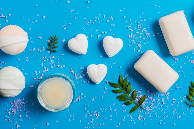 Salt spread on blue background with bath bombs; soap and cream Free Photo