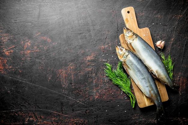Соленая сельдь с зубчиками чеснока и укропом. на темной деревенской поверхности Premium Фотографии
