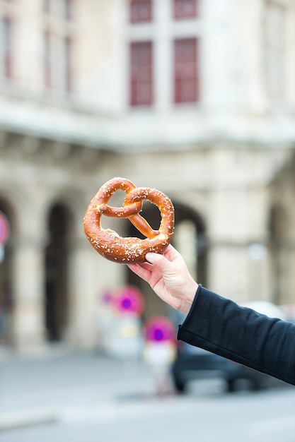 Salted pretzel in the hands of a man on background of the vienna opera Premium Photo