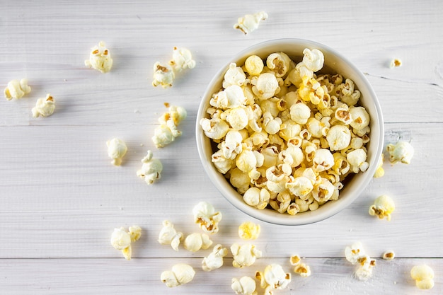 Salty popcorn in a blue cup is on a wooden table. popcorn lies around the bowl. top view. Premium Photo