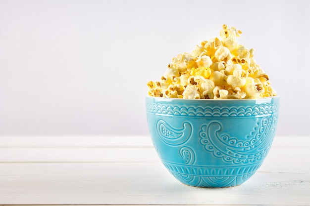 Salty popcorn in a blue cup is on a wooden table. Premium Photo