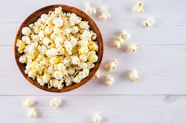 Salty popcorn in a wooden cup is on a white table. popcorn lies around the bowl. top view. Premium Photo