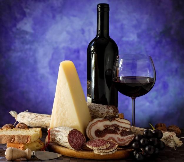 Salumi cheese, and glass of red wine Premium Photo