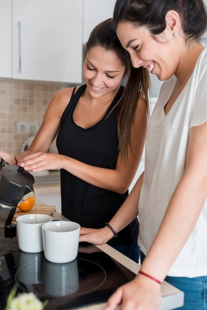 Same-sex couple pouring coffee in kitchen Free Photo