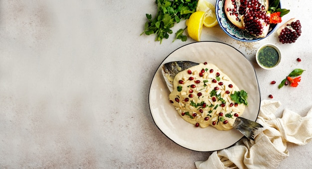 タヒニソース、ザクロの種子、アーモンドを添えたレバノンの魚(samke harra) Premium写真