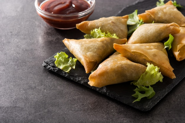 Samsa or samosas with meat and vegetables on black. traditional indian food. Premium Photo