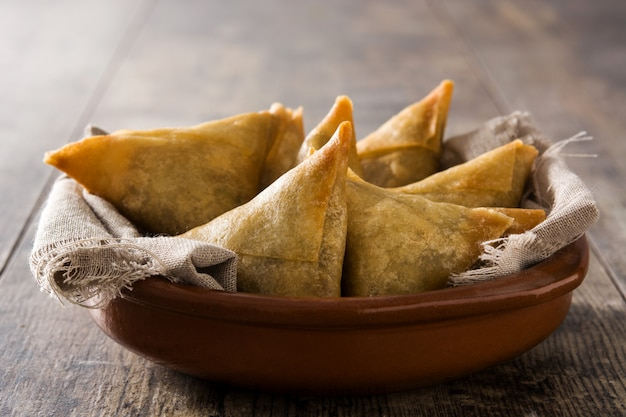 Samsa or samosas with meat and vegetables in bowl on wooden table. traditional indian food Premium Photo