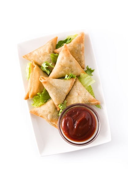 Samsa or samosas with meat and vegetables isolated on white. traditional indian food. top view. Premium Photo