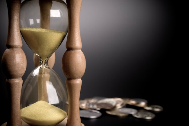 Sand clock and coins on black background Premium Photo