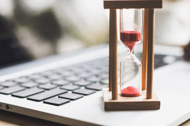 sand clock timer on laptop symbol of time photo premium download