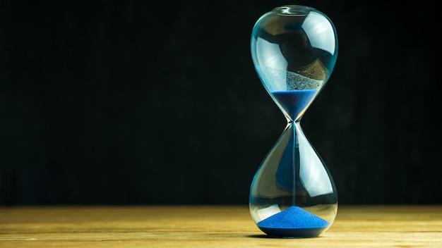 Sand clock on wooden table Premium Photo