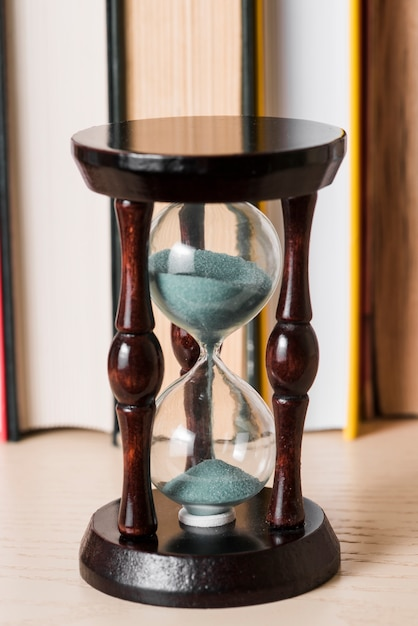 Sand falling in transparent hourglass on wooden desk Free Photo