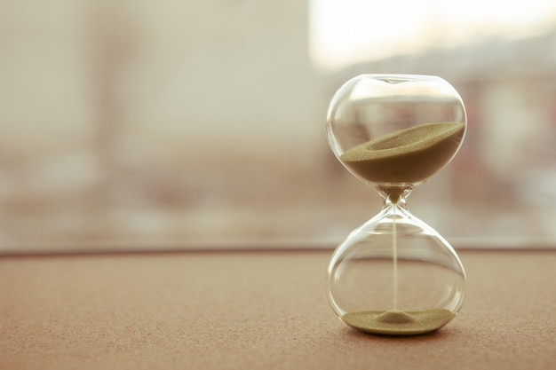 Sand running through the bulbs of an hourglass measuring the passing time Premium Photo