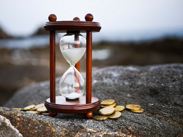 Sand running through the shape of hourglass with coins on rock background. time investment and retirement saving. Premium Photo