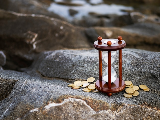 Sand running through the shape of hourglass with coins on rock background. Premium Photo