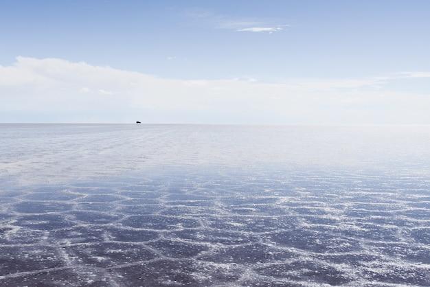 Текстура песка видна под кристально чистым морем и небом Бесплатные Фотографии