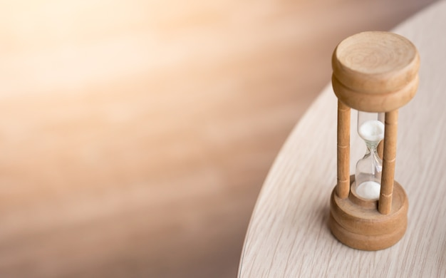 Sand watch on the wood table Premium Photo