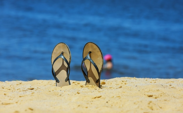 Sandal flip flop on the white sand beach with blue ocean background in vacations Premium Photo