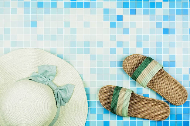 Sandals and a beach hat on blue ceramic tiles at the pool. - summer holiday concept. Premium Photo
